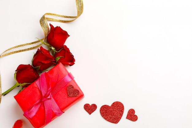 Rose rosse e confezione regalo su sfondo bianco. Foto Premium