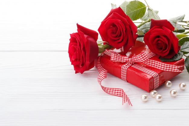 Rose rosse e una confezione regalo Foto Premium