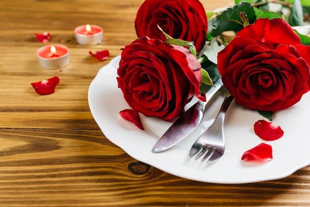 Rose rosse sul piatto bianco Foto Gratuite