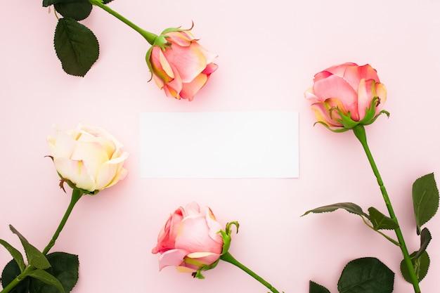 Rose sul rosa con un biglietto di auguri vuoto Foto Gratuite