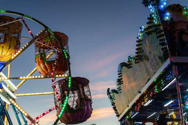 Rotella di ferris dei bambini decorata con molte luci e disegni al crepuscolo ad una fiera di natale. Foto Premium