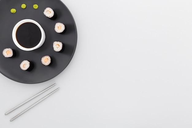 Rotoli di sushi di vista superiore e salsa di soia con lo spazio della copia Foto Gratuite
