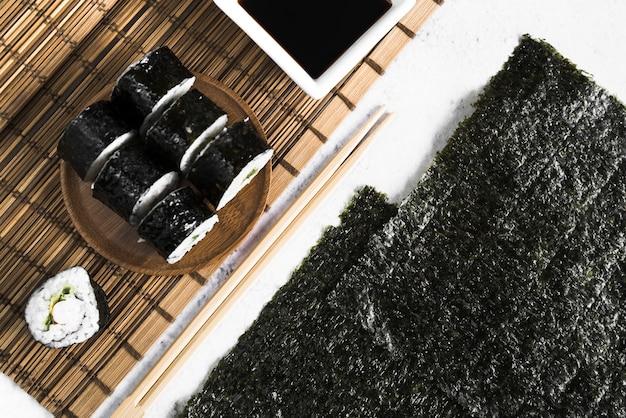 Rotoli di sushi e salsa di soia sulla stuoia di bambù vicino alle alghe Foto Gratuite