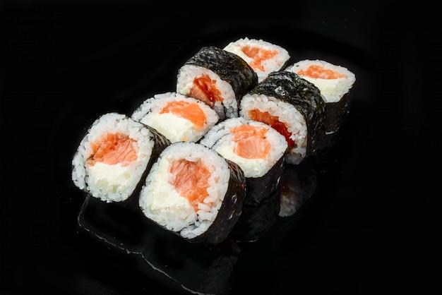 Rotoli di sushi giapponesi freschi tradizionali su un fondo nero Foto Premium