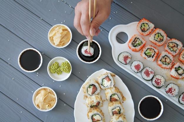 Rotoli di sushi mangiatori di uomini sulla tavola di legno grigia Foto Premium