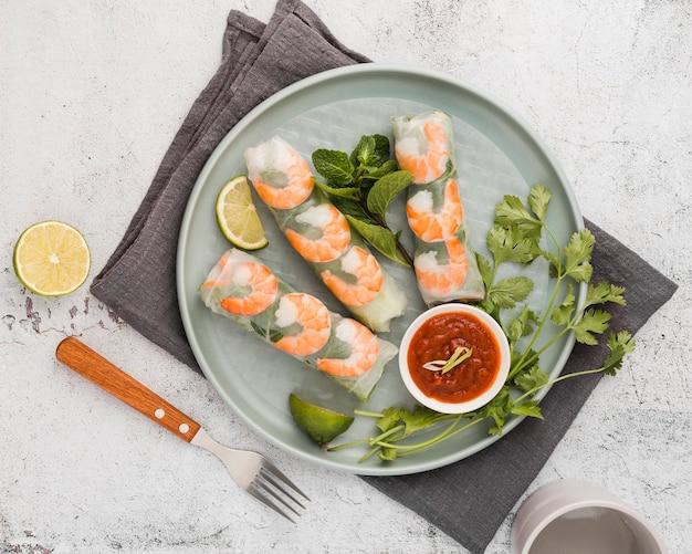Rotoli freschi del gamberetto sul piatto con salsa Foto Gratuite