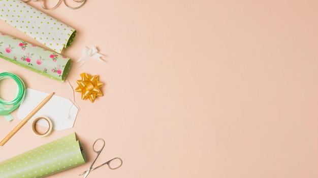 Rotolo di carta da imballaggio; nastro adesivo; matita; fiocchi di nastro e forbici disposti in superficie di pesca con spazio per il testo Foto Gratuite