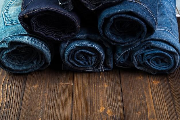 Rotolo di jeans sfilacciati o collezione di jeans blue jeans su legno scuro grezzo Foto Premium