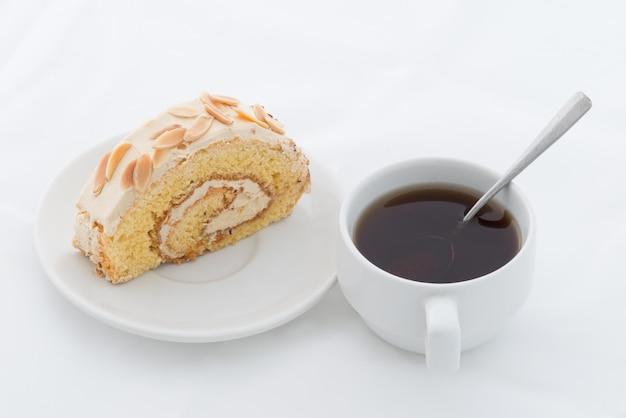 Rotolo di mandorle torta sul piatto bianco con bevanda calda Foto Premium