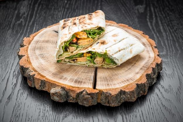 Rotolo di panino con il primo piano di bastoncini di pesce, formaggio e verdure sul tavolo Foto Premium