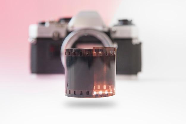 Rotolo di pellicola da 35 mm in ascesa sulla fotocamera slr sfocata Foto Premium