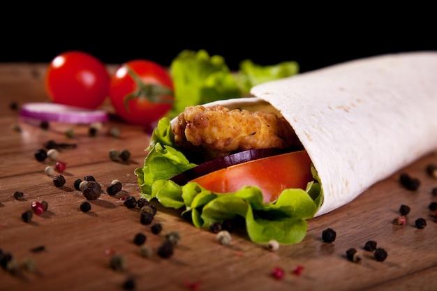 Rotolo di pollo con la cipolla e il pepe del pomodoro della lattuga su una tavola di legno e su un fondo nero. Foto Premium