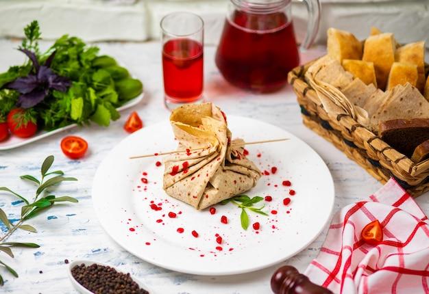 Rotolo di snack lavash con formaggio e semi di granato, pane, verdure e sorbetto su un piatto bianco. spuntino Foto Gratuite
