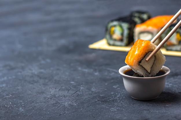 Rotolo di sushi con salmone con le bacchette sopra una ciotola con salsa di soia. cibo tradizionale giapponese. Foto Premium