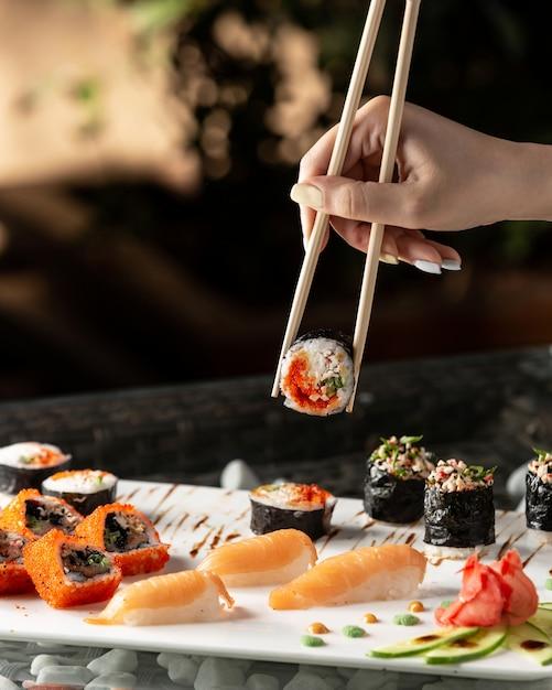 Rotolo di sushi della tenuta della donna con le bacchette Foto Gratuite