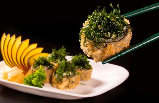 Rotolo di sushi fritto caldo con gamberetti, cetriolo e formaggio philadelphia. menu di sushi. cibo giapponese. futomaki Foto Premium