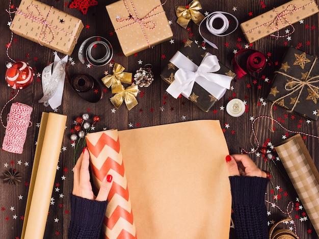 Rotolo di svolgimento della mano della donna di carta kraft di spostamento per l'imballaggio del contenitore di regalo di natale Foto Gratuite