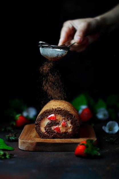 Rotolo dolce della fragola del cioccolato con le fragole levitanti e le mani della donna, fotografia scura dell'alimento Foto Premium