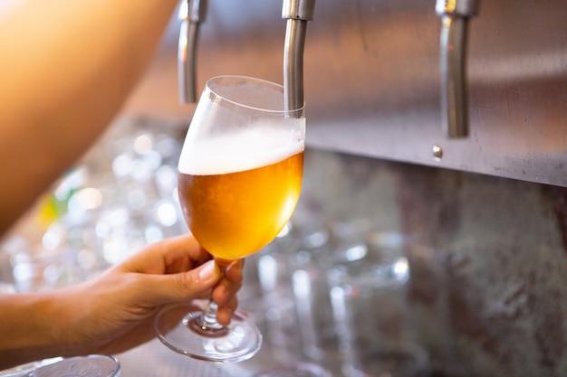 Rubinetto della birra al bar e rinfresco freddo per l'alcol adulto dopo il lavoro Foto Premium