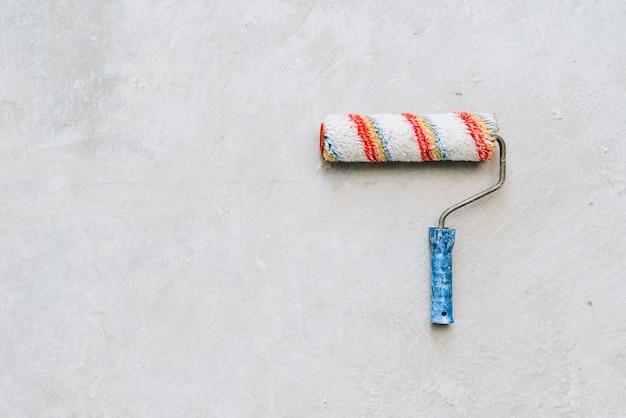 Rullo di vernice con una maniglia blu isolata sul pavimento di cemento con spazio per il testo Foto Premium