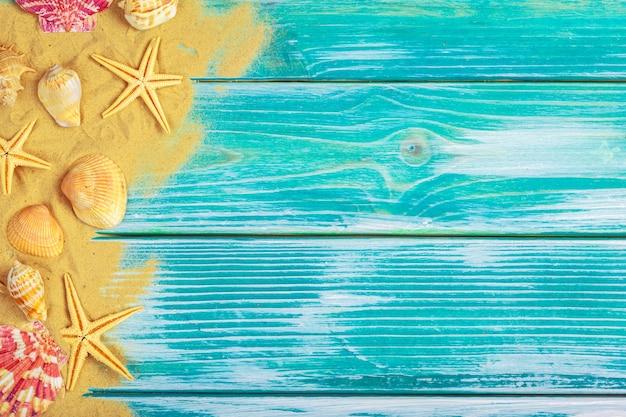 Sabbia di mare e conchiglie su fondo di legno blu Foto Premium