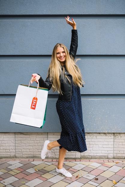 Sacchetti della spesa allegri della tenuta della giovane donna che poising contro la parete Foto Gratuite