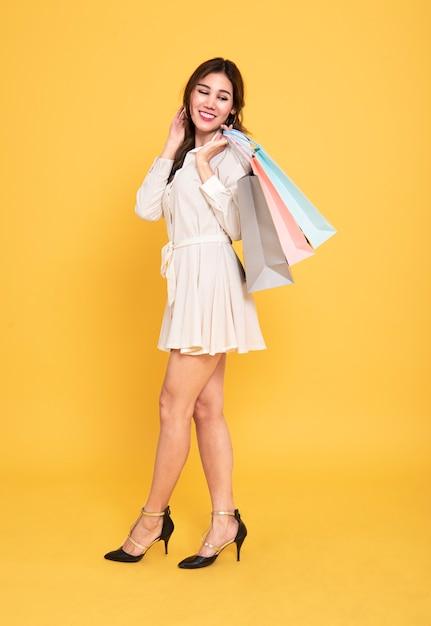 Sacchetti della spesa d'uso della tenuta del vestito dalla bella ragazza asiatica del ritratto su fondo giallo. Foto Premium