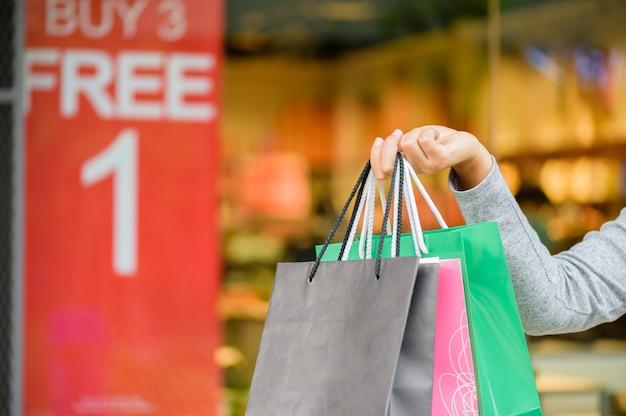 Sacchetti della spesa della tenuta della donna nel centro commerciale, concetto di vendita di black friday. Foto Premium