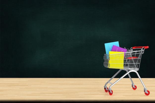 Sacchetti della spesa di carta variopinti in carrello sulla tavola di legno con il contesto del bordo nero Foto Premium