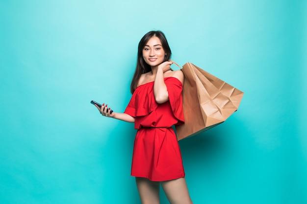 Sacchetti della spesa e invio di messaggi di testo di trasporto della giovane donna asiatica sul telefono isolato sulla parete verde Foto Gratuite