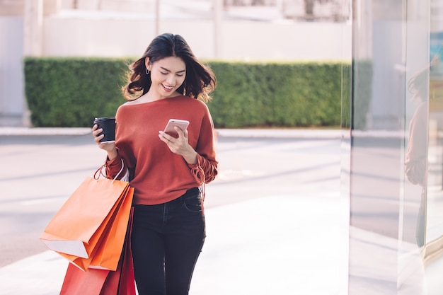 Sacchetti della spesa graziosi asiatici felici della tenuta della ragazza sul concetto del centro commerciale. Foto Premium