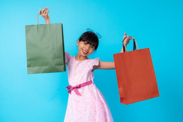 Sacchetto della spesa alla moda della tenuta del giovane bambino asiatico felice della ragazza, stile di vita del concetto pagato di stile di modo dei bambini Foto Premium