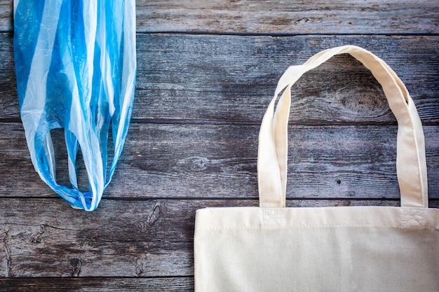 Sacchetto della spesa di eco contro un sacchetto di plastica su fondo di legno, strato piano. salva il pianeta terra Foto Premium