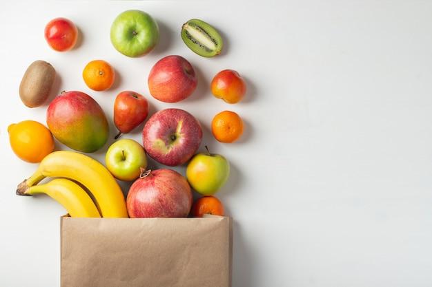 Sacchetto di carta di diversi frutti sani su un tavolo. Foto Premium