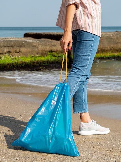 Sacchetto di immondizia della tenuta della donna con la bottiglia di plastica riciclabile Foto Gratuite