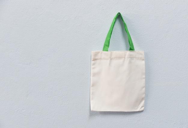 Sacco di acquisto del panno del sacchetto della borsa di eco del tessuto della tela del totalizzatore bianco sul fondo della parete Foto Premium