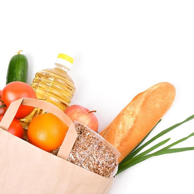 Sacco di carta con forniture alimentari per il periodo di isolamento in quarantena su un bianco. copyspace. Foto Premium