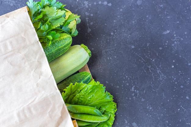 Sacco di carta delle verdure verdi sane differenti sulla tavola scura. il concetto di corretta alimentazione e cibo sano. alimenti biologici e vegetariani vista dall'alto, disteso, copia spazio per il testo. Foto Premium