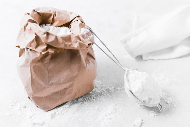 Sacco di carta vista frontale con farina e panno Foto Gratuite