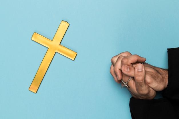 Sacerdote che prega con croce di legno Foto Gratuite