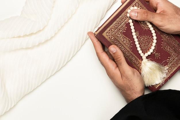 Sacerdote con libro sacro e braccialetto Foto Gratuite