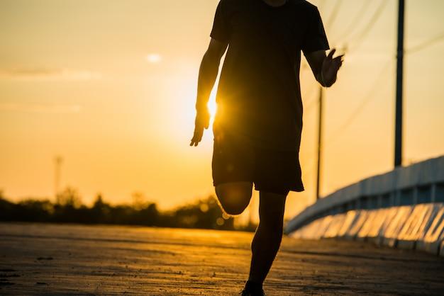 Sagoma di un uomo giovane fitness in esecuzione su sunrise Foto Gratuite