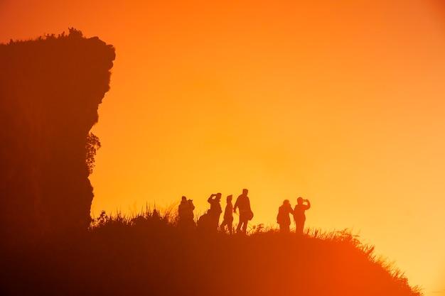Sagome di così tante persone in cima alle colline al buio in attesa del sorgere del sole. Foto Premium