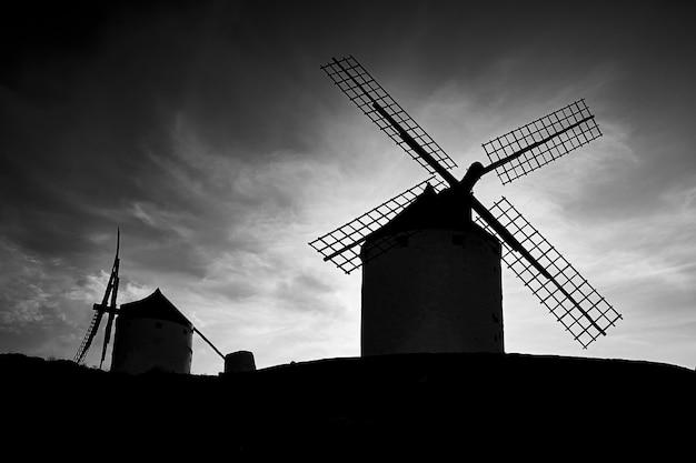 Sagome di vecchi mulini a vento in una giornata nuvolosa Foto Premium