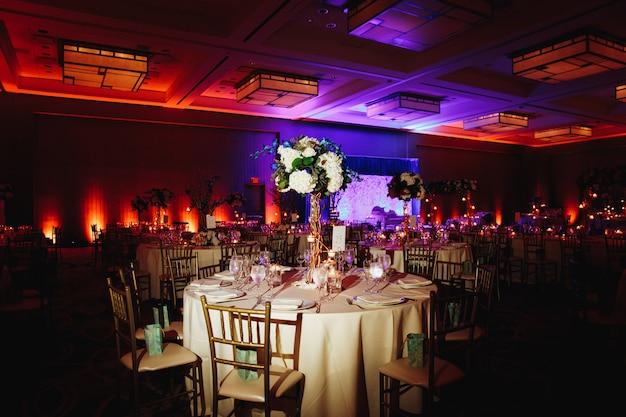 Sala per banchetti decorata con tavola rotonda servita con centrotavola di ortensia e sedie chiavari Foto Gratuite