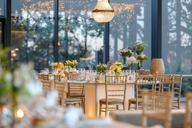 Sala per matrimoni decorata con una bellissima tavola con decorazioni floreali Foto Gratuite