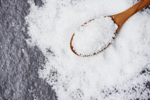 Sale in cucchiaio di legno e mucchio di sale bianco su oscurità Foto Premium