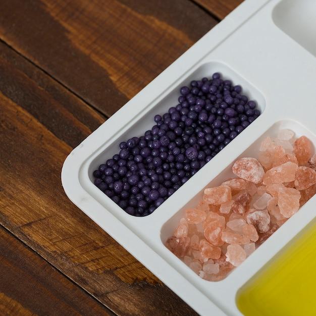 Salgemma alle erbe; prodotti cosmetici di mirtilli e olio sul piatto bianco sopra la scrivania in legno Foto Gratuite