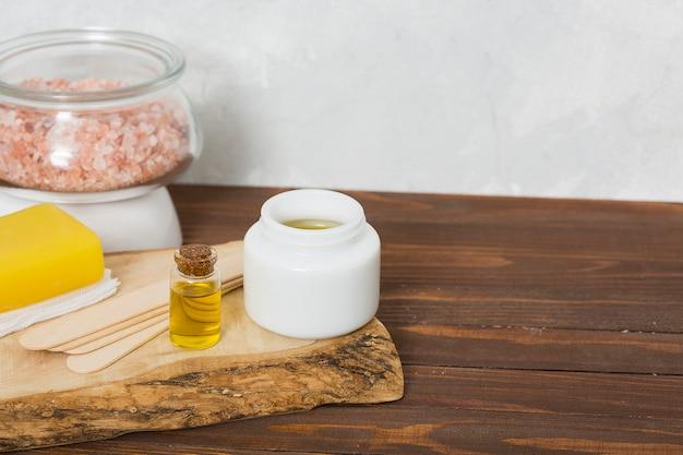 Salgemma himalayano in barattolo di vetro; bastoncini di cera di legno; miele; sapone giallo a base di erbe e bottiglia di olio essenziale sul tavolo Foto Gratuite