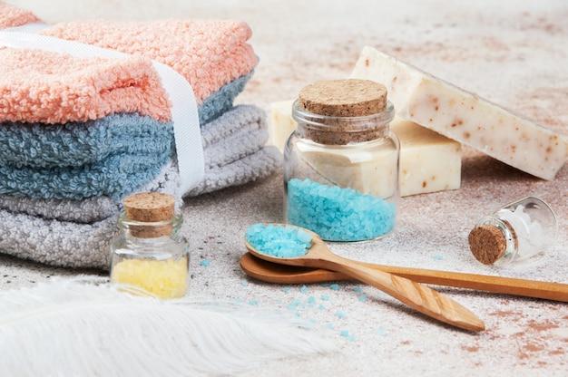 Sali da bagno in bottiglie di vetro, cucchiaio di legno Foto Premium